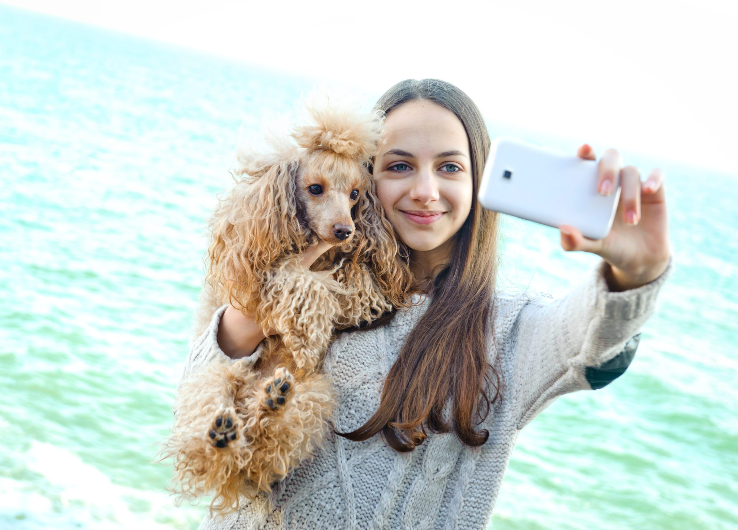 Girl taking selfies of herself and dog.